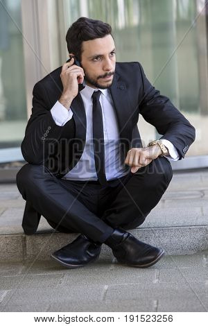 handsome businessman sitting outside on the curb and talking on phone