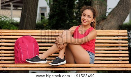 A Student Sitting On A Park Bench