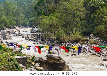 Landscape photo of prayer flag and mountain stream