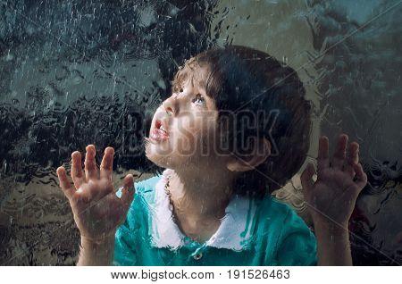 child and window on a wet rainy day. Little boy behind a rain-splattered window