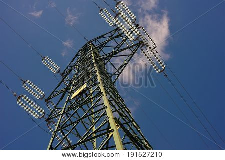 Metallic structure of an electric pylon on blue sky background