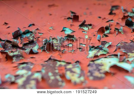 Red flaking paint on on blue old metal surface. Old metal texture for background