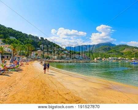 View of the beach of Port de Soller with people lying on sand and the old buildings visible in background, Soller, Palma de Mallorca, Balearic islands, Spain.
