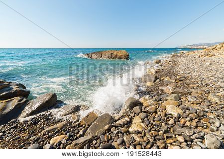 Water Waves Breaking On Gravels, Pebbles And Boulders Of An Empty Beach In The Harsh Rocky Coastline