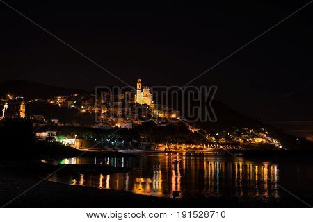 The Historical Town Of Cervo Glowing In The Night Under Moonlight And Starry Sky On The Coastline Of