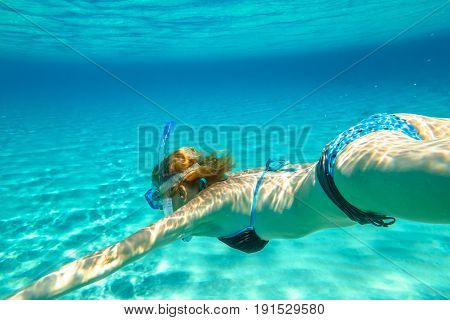 Female apnea bikini swims in crystal trapical sea. Underwater scene of a woman snorkeling and doing free diving. Watersport activity in summer vacations. Tropical destination and leisure concept.