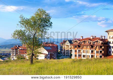 Bansko, Bulgaria - June 13, 2017: Wooden chalet hotel houses and summer mountains panorama in bulgarian all season resort