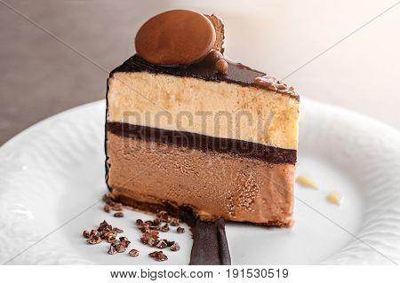 Delicious vanilla ice cream cake, coffee and three layer chocolate, served with chocolate chips covered by a layer of chocolate on a white rectangular plate, on wooden table background.