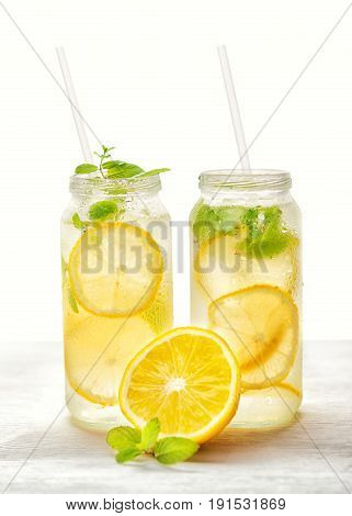Lemonade With Fresh Lemon And Twig Mint With Drinking Straw On White Background