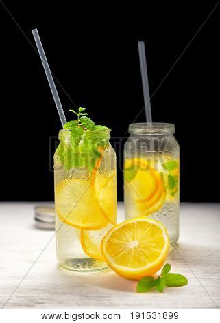 Homemade Lemonade With Fresh Lemon And Twig Mint With Drinking Straw On Black Background