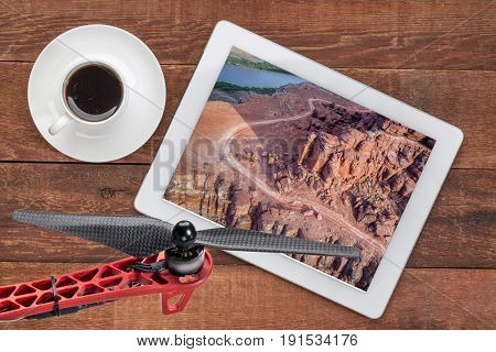 Chicken Corner Road on the edge of Colorado River Canyon in the Moab area, Utah, reviewing aerial picture on a tablet with cup of coffee