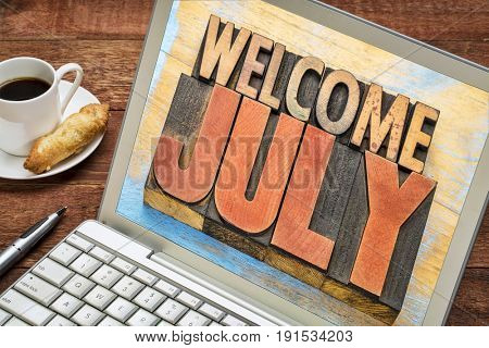 Welcome July banner - word abstract in vintage letterpress wood type blocks on a laptop screen with coffee