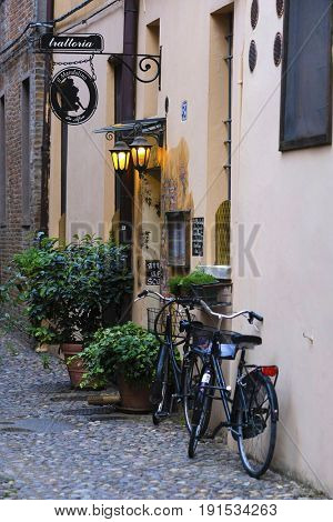 Bicycle parked near the wall of an ancient house in an Old Town of Ferrara, Italy