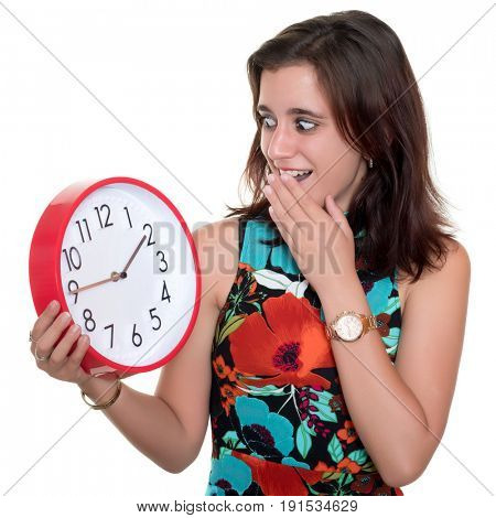 Beautiful teenage girl with a surprised expression checking the time on a big clock - Useful to illustrate lateness or the passing of time