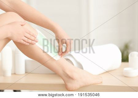 Young woman epilating legs with wax strip at home