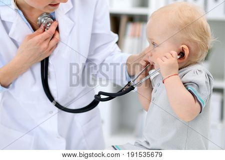 Pediatrician is taking care of baby in hospital. Little girl is being examine by doctor with stethoscope. Health care, medicine and help concept.