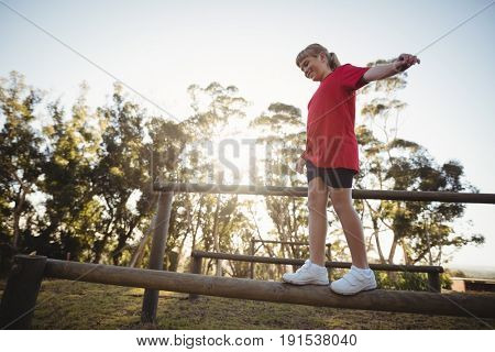 Girl walking on obstacle during obstacle course in boot camp