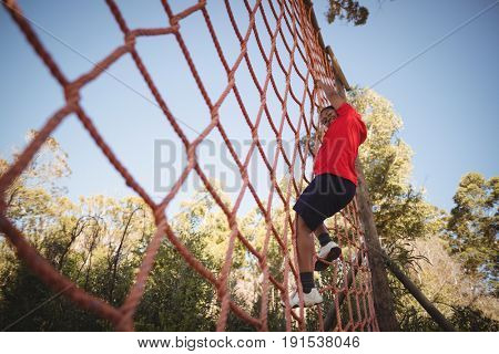 Portrait of happy boy climbing a net during obstacle course in boot camp