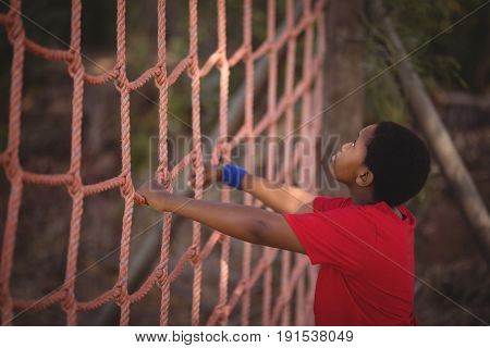 Determined boy climbing a net during obstacle course in boot camp