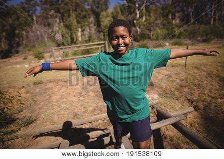 Portrait of happy boy walking on obstacle during obstacle course in boot camp