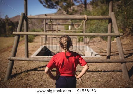 Rear view of girl looking at outdoor equipment during obstacle course in boot camp