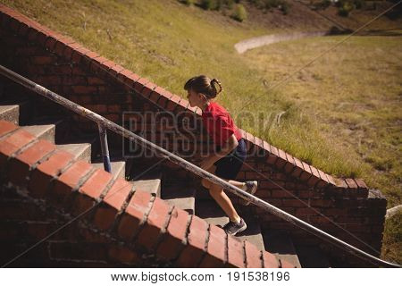 Determined girl running upstairs during obstacle course in boot camp