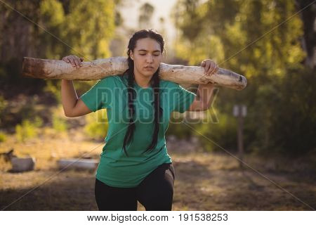 Woman carrying heavy wooden log during obstacle course in boot camp