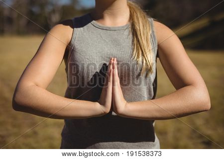 Mid section of woman praising yoga during obstacle course in boot camp