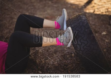 Low section of woman exercising with huge tyre during obstacle course in boot camp