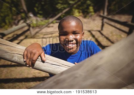 Portrait of happy boy standing in boot camp during obstacle course