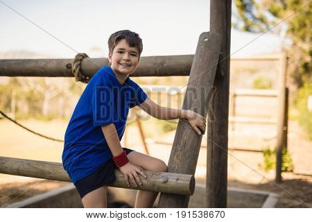 Portrait of happy boy sitting on outdoor equipment during obstacle course in boot camp