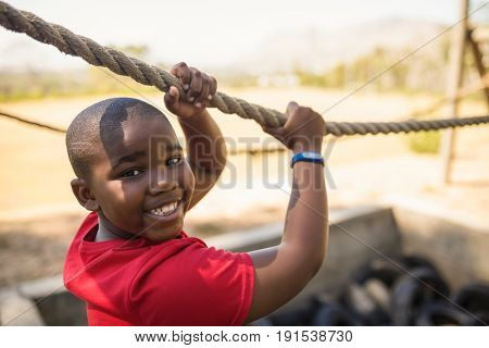 Portrait of happy boy crossing the rope during obstacle course in boot camp