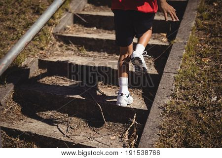 Low section of girl running upstairs during obstacle course in boot camp