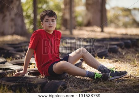 Portrait of boy relaxing on tyre during obstacle course during obstacle course in boot camp