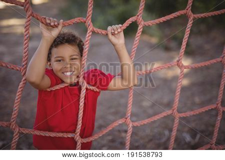 Portrait of happy boy leaning on net during obstacle course in boot camp