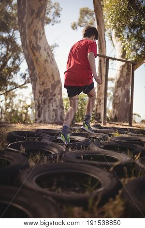 Boy running over tyres during obstacle course in boot cam