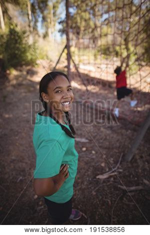 Portrait of girl standing with hands on hip during obstacle course in boot camp