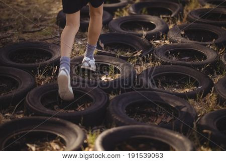 Low section of girl running over tyres during obstacle course