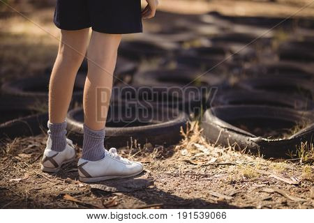 Low section of girl standing near tyre during obstacle course in boot camp