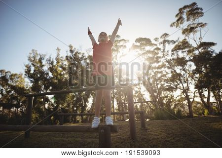 Happy boy cheering on obstacle during obstacle course in boot camp