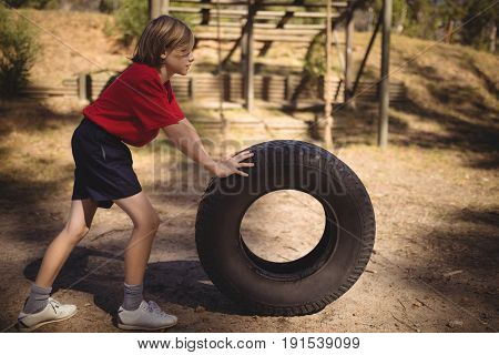 Determined girl exercising with huge tyre during obstacle course in boot campboot, camp, boot camp, sunny, summer, park, kid, sportswear, athlete, athletic, obstacle course, obstacle, sports,