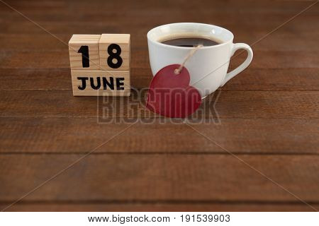 High angle view of calender date by coffee cup with heart shape on wooden table