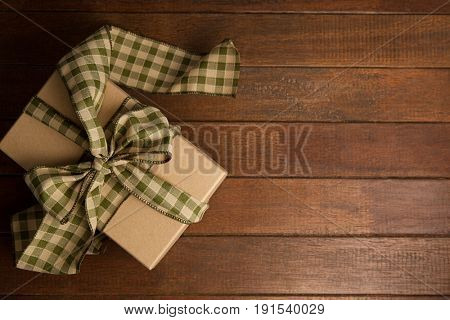 Overhead view of gift box on brown wooden table
