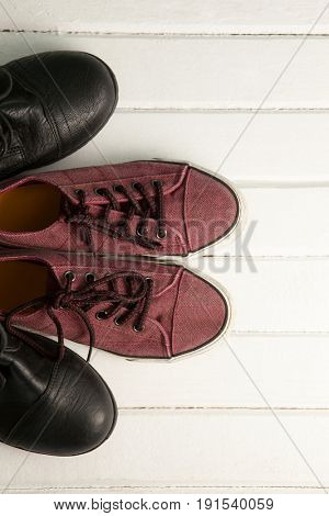 Overhead view of brown loafers and black shoes on white wooden floor