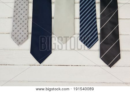 High angle view of various neckties on wooden table
