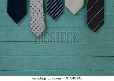Close up of various neckties hanging on green wooden wall