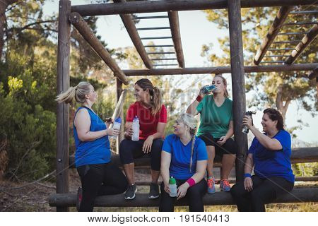 Group of women drinking water in the boot camp on a sunny day
