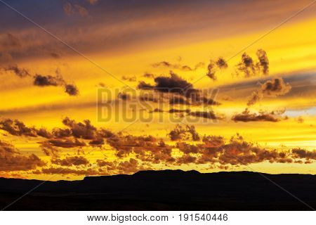 Unusual storm clouds at sunset. Bright red and orange colors of the sky. Suitable for background.