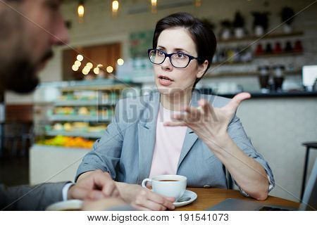 Portrait of confident modern businesswoman meeting with partner in cafe discussing work and gesturing actively