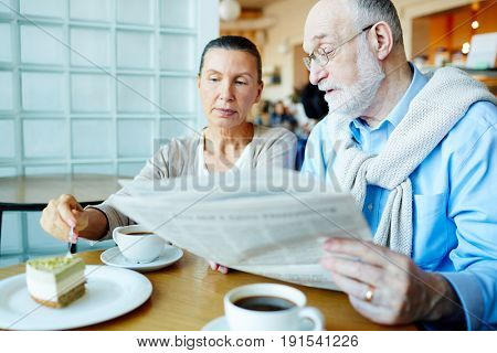 Modern seniors discussing latest news by dessert in cafe